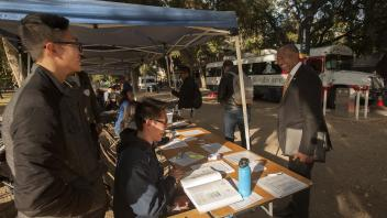 Anthony Nguyen, a biological science major, and Bryan Heng, a biology major, greet UC Davis Chancellor Gary May when he dropped by to thank them for their work during the BloodSource blood drive on the Quad on Tuesday November 7, 2017.