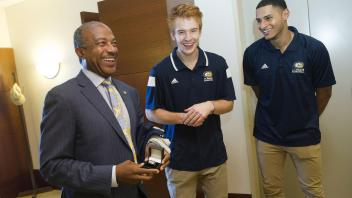 UC Davis men's basketball players Siler Schneider, Roger Printup and Chima Moneke (not pictured) and coach Jim Les (not pictured) visit Chancellor Gary May to give him his own Championship Basketball ring.