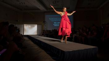 LeShelle May, wife of Chancellor May, models a student-designed dress for the Picnic Day Fashion Show. The Red Dress collection is part of a national symbol encouraging women to reduce their risks of heart disease.