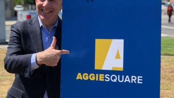 Mayor Steinberg poses for a photo next to the Aggie Square poster on the UC Davis Health campus.