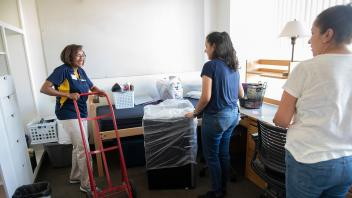 Helene Dillard, Dean of the College of Agriculture and Environmental Sciences helps new students move-in to the Segundo residence halls.