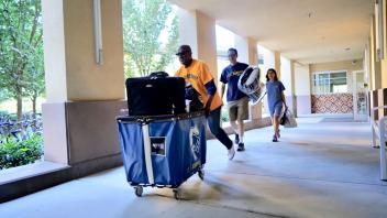 UC Davis Chancellor, Gary May helps a family of a new student move-in to the Tercero Residence halls.