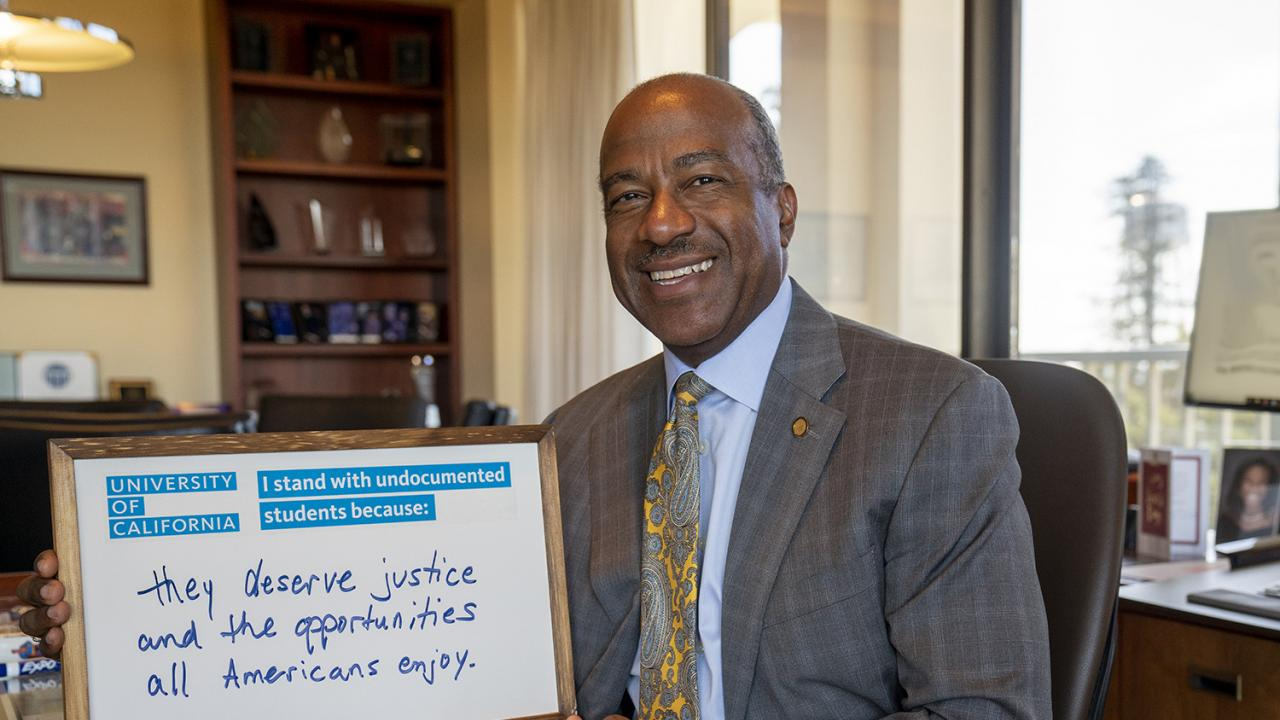 Chancellor May looking at the camera smiling, holding a dry erase board that states: I stand with undocumented students because they deserve justice and the opportunities all Americans enjoy.