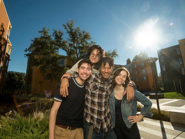A group of UC Davis Students smiles in front of on campus housing