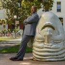 Chancellor May leaning on an Egghead in front of Mrak Hall.