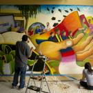 UC Davis Student Community Center mural of graduating students in colorful landscape