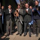 Seven people clap and smile during a ribbon-cutting ceremony.