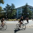 Students ride bicycles in front of Shields Library.