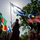 Parade participants carry flags of various nations.