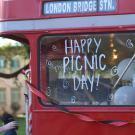 "Red double decker bus with ""Happy Picnic Day!"" on the window"