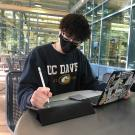 Student with mask working on laptop and tablet with UC Davis sweatshirt