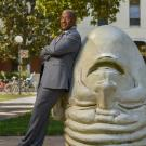 "Chancellor Gary S. May, in suit, leans against ""Eye on Mrak"" Egghead sculpture."